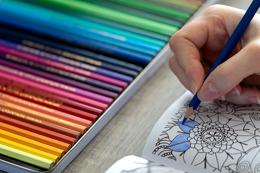 Person holding a blue color pencil while coloring a book